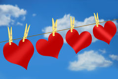 Red hearts on clothesline against blue sky Stock Image