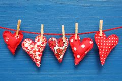 Red hearts with clothespins. Homemade sewn hearts hanging on a line by wood clothespins against a blue woodgrain wall Royalty Free Stock Images