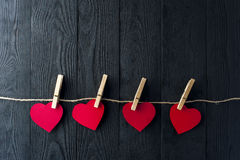 Red hearts with clothespins on dark background Stock Photography
