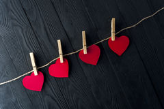 Red hearts with clothespins on dark background Stock Image