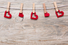 Red hearts with clothespins on a leash hung. In front of rustic wooden background with text space as a greeting for Valentine's Dayn Royalty Free Stock Image