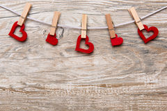 Red hearts with clothespins on a leash hung in front of rustic wooden background with text space as a greeting for Valentine's Day Stock Image