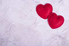 Red hearts on concrete background. Two hearts on a beige table. Valentines day and love concept stock image