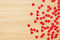 Red hearts confetti on wooden background stock image