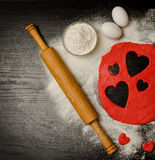 Red hearts cut out dough with eggs and flour on a black table, a rolling pin. View from above. Royalty Free Stock Photos