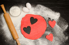 Red hearts cut out dough with rolling pin, eggs and flour on a black table . View from above. Space for text Royalty Free Stock Photos
