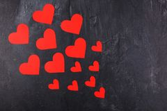 Hearts go from the smaller to the larger diagonally to the left on a stone background. Red hearts of different sizes go from the smaller to the larger diagonally royalty free stock photography