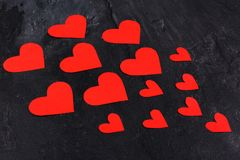 Hearts go from the smaller to the larger are directed to the left close-up on a stone background. Red hearts of different sizes go from the smaller to the larger royalty free stock photography