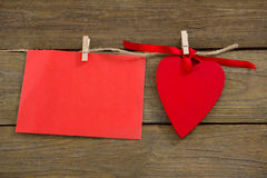 Red hearts and envelope with cloth peg hanging on rope. Against wooden plank Stock Photo