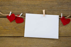 Red hearts and envelope with cloth peg hanging on rope. Against wooden plank Stock Photos