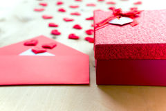 Red hearts with envelope and gift box on wooden background. Writing love letter. Happy Valentine`s day concept. Horizontal composition Stock Image