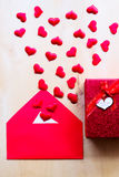 Red hearts with envelope and gift box on wooden background. Writing love letter. Happy Valentine`s day concept. Vertical composition Royalty Free Stock Image