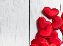 Red hearts fabric on a background of white boards Stock Photos