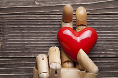 Red hearts and fake wooden hand on planks Royalty Free Stock Photography