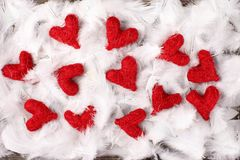 Red hearts on feathers. Red hearts on white feathers Royalty Free Stock Images