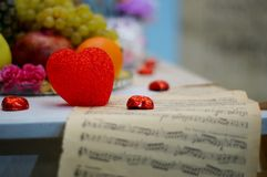 Red hearts on festive table and sheet with notes.  Royalty Free Stock Photos