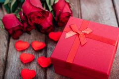 Red hearts, flower roses and gift box on wooden background royalty free stock image