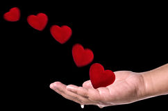Red hearts fly into hand on black  background . Love concept Stock Photos