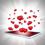 Red hearts fly out of the tablet PC Royalty Free Stock Image