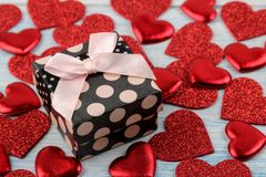 Red hearts and gift box closeup on a blue wooden background. Valentine`s Day royalty free stock image
