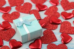 Red hearts and gift box closeup on a blue wooden background. Valentine`s Day stock images