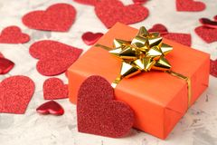 Red hearts and gift box closeup on a light concrete background. Valentine`s Day royalty free stock images
