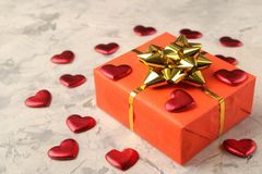 Red hearts and gift box closeup on a light concrete background. Valentine`s Day royalty free stock photos