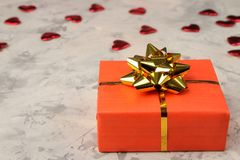 Red hearts and gift box closeup on a light concrete background. Valentine`s Day stock photography