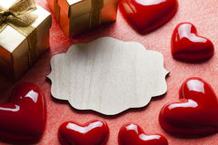Red hearts, gift boxes and wooden label Stock Images