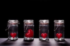 Red Hearts in Glass Jars. On black royalty free stock photo