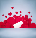 Red hearts on a gray background with a card for the text. Stock Photos