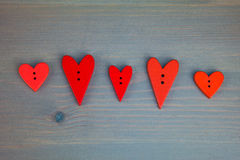 Red hearts on grey wooden background. Button love. Stock Photo