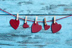 Red hearts hanging in a clothes line. Some hearts, made with red corrugated paperboard, hung with clothespins in a clothes line, against a blue rustic wooden Stock Photography