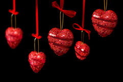 Red hearts hanging over black Stock Photography