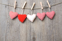 Red hearts hanging over wood background Royalty Free Stock Images