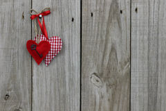 Red hearts hanging on wood background. Red gingham (checkered) and red heart with red ribbon hanging from rope on wood door Stock Images