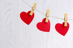 Red hearts hanging on wooden background Royalty Free Stock Images