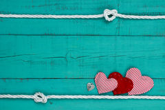 Red hearts and heart lock by rope border against teal blue wooden background Royalty Free Stock Photos
