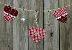 Red hearts and heart-shaped locks hanging on clothesline by distressed wood fence Stock Image