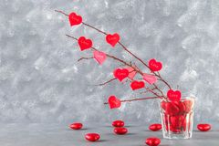 Red hearts with an inscription Love hang on branches on a gray concrete background. Love tree. The concept of Valentine's Day. A. Symbol of love Stock Photo