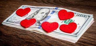 The red hearts lie on the bundle of dollar bills. I love money_ royalty free stock photography
