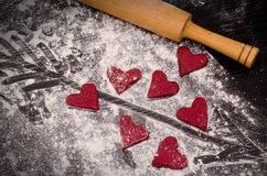 Red hearts made of dough, wooden rolling pin and an arrow painted on flour Royalty Free Stock Photo