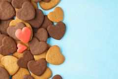 Red hearts made of glazed gingerbreads over a bunch of cookies stock image