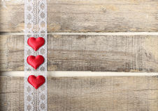 Red hearts on old wooden background. Three red hearts on old wooden background with lace Stock Photos