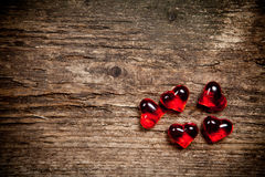 Red hearts on old wooden table Stock Images