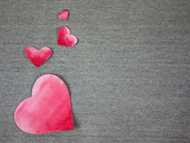 Red hearts. Red painted paper hearts on grey fabric Stock Photography