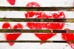 Red hearts painted on a white wooden bench. Love concept royalty free stock image