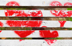 Red hearts painted on a white wooden bench. Love concept royalty free stock photography