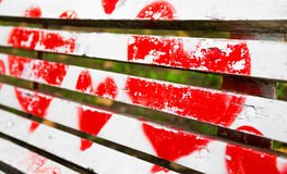 Red hearts painted on a white wooden bench. Love concept stock images
