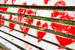 Red hearts painted on a white wooden bench. Love concept stock photos